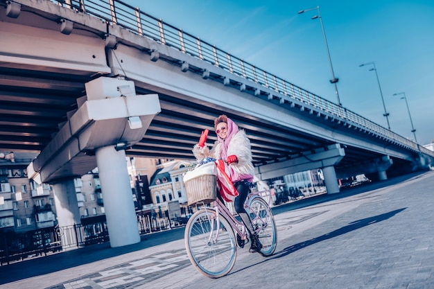 Freudige stimmung. schöne internationale frau, die lächeln auf ihrem gesicht hält, während fahrrad fährt