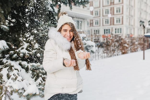 Freudige süße frau, die spaß mit schneeflocken im freien auf tannenbaum voll mit schnee hat. junges charmantes modell in der warmen winterkleidung, die kaltes schnee auf straße genießt. positivität ausdrücken, lächeln.