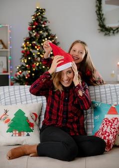 Freudige tochter setzt weihnachtsmütze auf mutterkopf, der auf couch sitzt und weihnachtszeit zu hause genießt
