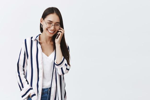 Freudige und erfolgreiche junge modefrau, die am telefon spricht und unterhaltung genießt. sorglose entspannte frau in gestreifter bluse und brille, mit niedlichem lächeln herabblickend, smartphone haltend