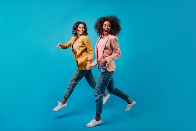 Freudige weibliche modelle, die auf blauer wand laufen