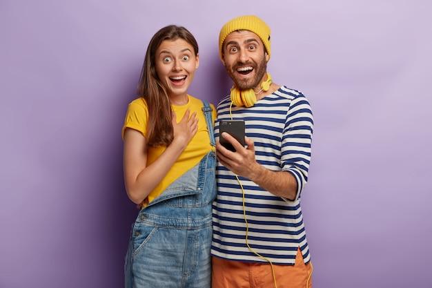 Freudige weibliche und männliche teenager halten smartphone-gadget, gekleidet in stilvolle kleidung