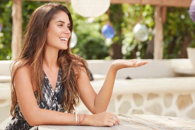 Freudige wunderschöne frau mit positivem ausdruck, hält die hände hoch, erholt sich im terrassencafé, genießt sonniges wetter und warme luft.