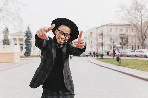 Freudiger afrikanischer kerl mit glücklichem lächeln, das auf der straße tanzt. romantischer junger mann mit brauner haut, die freizeit in der herbststadt genießt.