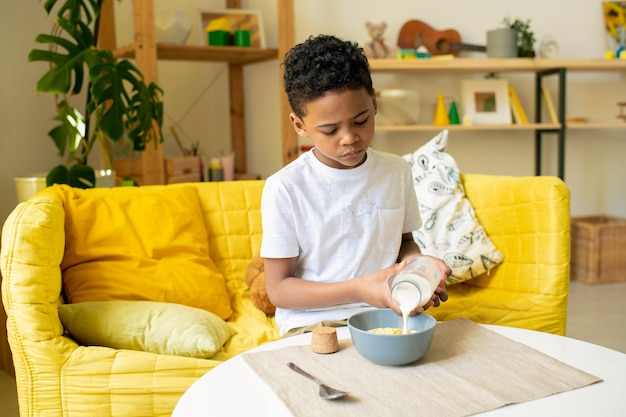 Freudiger afrikanischer kleiner junge im t-shirt, der ein stück essen in den mund steckt, während er auf der couch am tisch in der wohnzimmerumgebung sitzt
