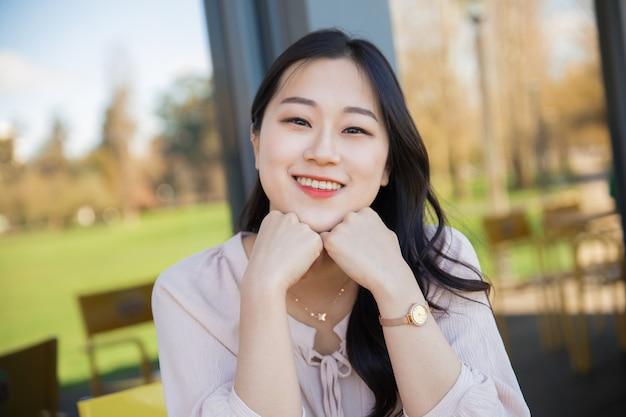 Freudiger asiatischer weiblicher tourist, der auf hotelterrasse sich entspannt