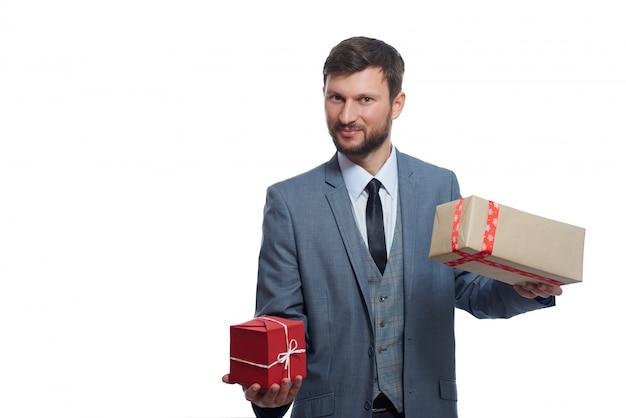 Freudiger bärtiger geschäftsmann, der zwei geschenkboxen hält, um lächelnd auf weiß zu wählen