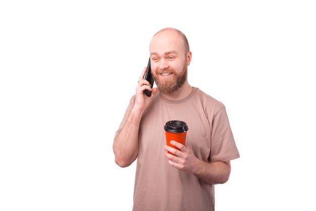 Freudiger bärtiger hipster-mann, der auf smartphone spricht und etwas kaffee trinkt
