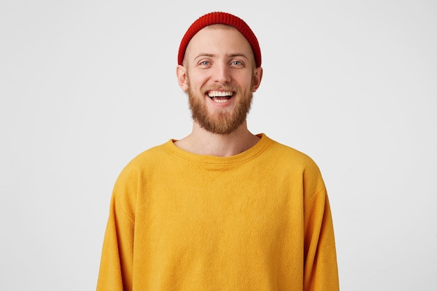 Freudiger bärtiger junger süßer mann lacht freudig, als er lustigen witz hört, roten hut und pullover trägt