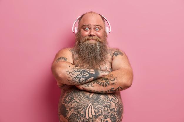 Freudiger bärtiger mann hält die hände über dem nackten körper gekreuzt, sieht glücklich aus, hört gerne musik, trägt kopfhörer an den ohren, hat den bauch tätowiert, hört lieblingslied. freizeit zu hause, lebensstil