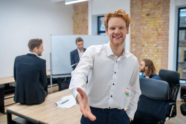 Freudiger begeisterter rothaariger mann im weißen hemd mit ausgestreckter handfläche und kollegen hinten im büro
