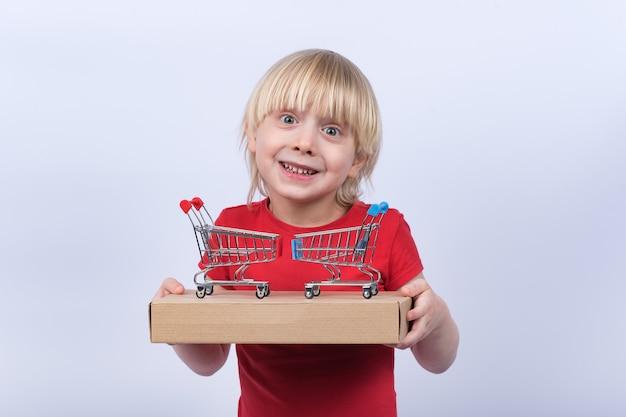 Freudiger blonder junge, der schachtel und spielzeug-einkaufswagen hält