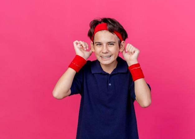 Freudiger dummer junger hübscher sportlicher junge, der stirnband und armbänder mit zahnspangen trägt, die kamera betrachten, die affenohren lokalisiert auf purpurrotem hintergrund mit kopienraum macht
