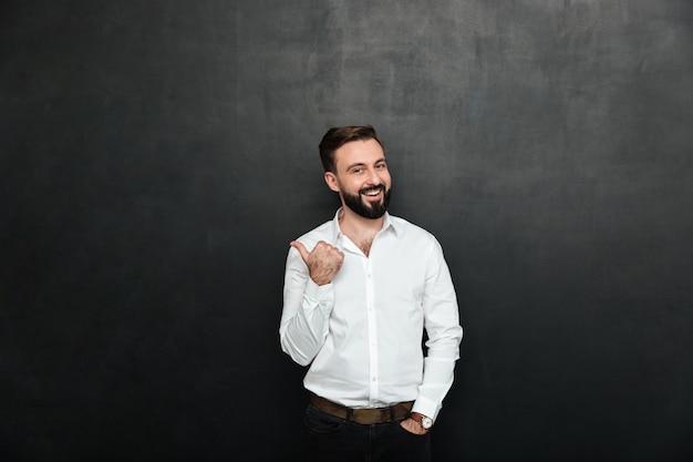 Freudiger erwachsener kerl im büro, das auf kamera aufwirft und beiseite mit dem daumen über dunkelgrauen kopienraum gestikuliert
