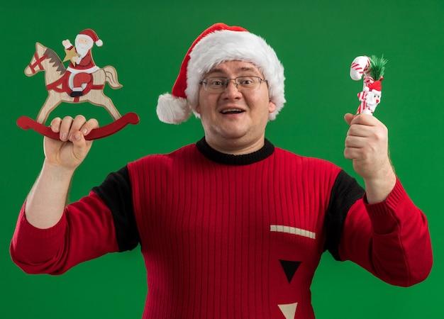 Freudiger erwachsener mann, der brille und weihnachtsmannhut hält, der weihnachtsmann auf schaukelpferdfigur und zuckerstangenverzierung hält, die kamera lokalisiert auf grünem hintergrund betrachtet