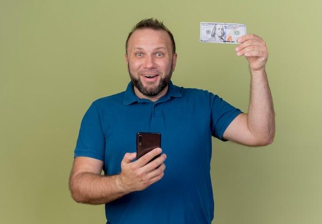 Freudiger erwachsener slawischer mann, der geld sammelt und handy hält