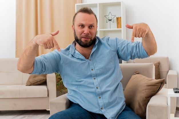 Freudiger erwachsener slawischer mann sitzt auf sessel und zeigt mit zwei händen nach unten im wohnzimmer