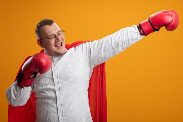 Freudiger erwachsener slawischer superheldenmann im roten umhang, der brille und kastenhandschuhe trägt, streckt hand aus, die seite betrachtet, die eine andere hand in der luft lokalisiert auf orange hintergrund hält