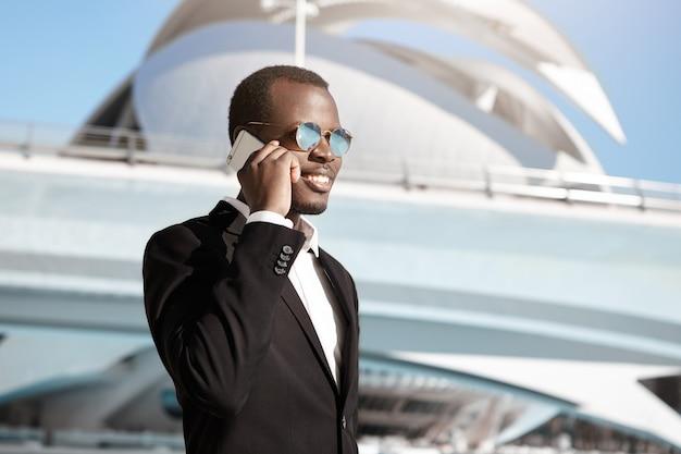 Freudiger geschäftsmann, der auf dem smartphone im freien auf seinem weg zum büro spricht