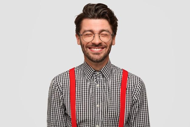 Freudiger glücklicher junger mann freiberufler träumt von etwas angenehmem, stellt sich gute ruhe vor, hat ein zahniges lächeln