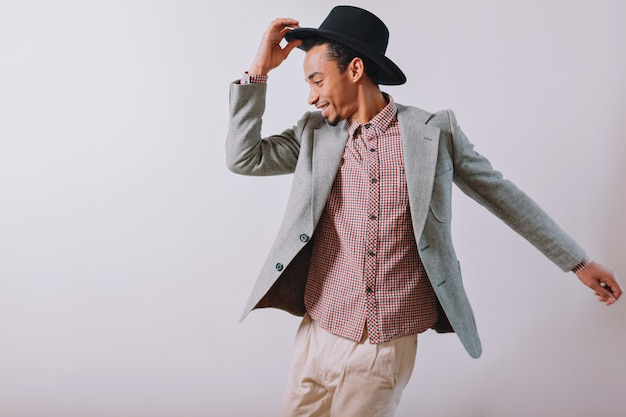 Freudiger glücklicher mann trägt schwarzen hut und grauen anzug, der mit aufgeregten gefühlen auf grau tanzt