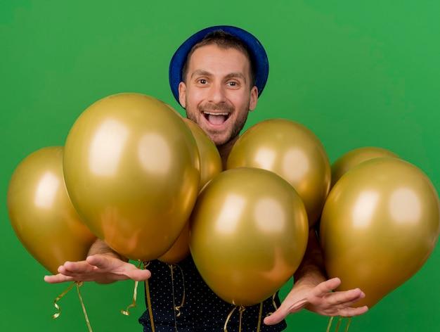 Freudiger gutaussehender mann, der blauen parteihut trägt, steht mit heliumballons, die ausgestreckte hände auf grüner wand mit kopienraum ausstrecken