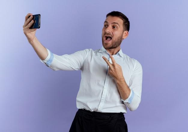 Freudiger gutaussehender mann gestikuliert siegeshandzeichen, das telefon lokalisiert auf lila wand betrachtet
