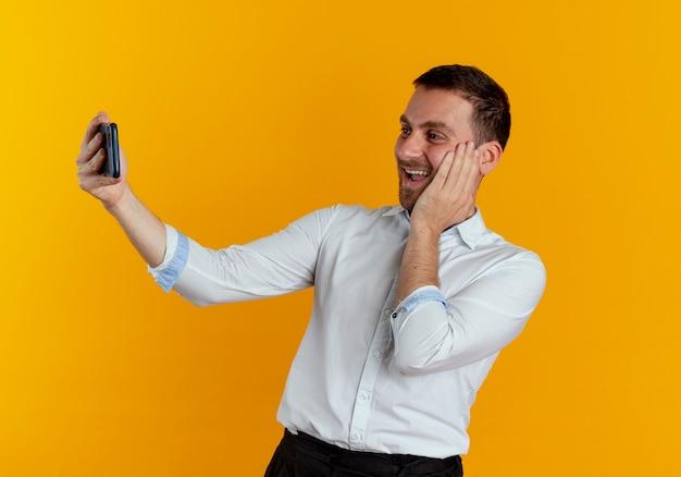 Freudiger gutaussehender mann legt hand auf gesicht, das telefon betrachtet, das selfie lokalisiert auf orange wand nimmt