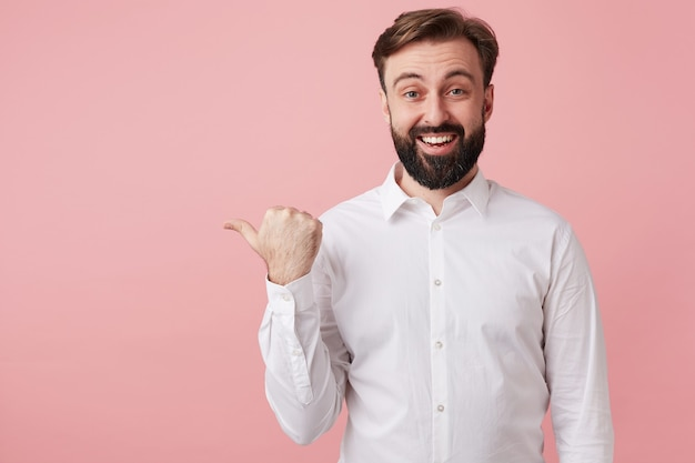 Freudiger hübscher bärtiger brünetter kerl mit kurzem haarschnitt, der glücklich nach vorne mit breitem lächeln schaut und hand mit daumen hebt, während er über rosa wand steht