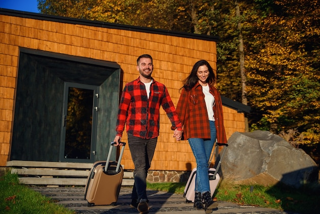 Freudiger hübscher bärtiger junger mann und hübsche stilvolle frau, die vom modernen haus mit koffern ausgehen, während sie zusammen zur urlaubsreise gehen.