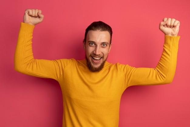 Freudiger hübscher blonder mann, der fäuste auf rosa erhebt