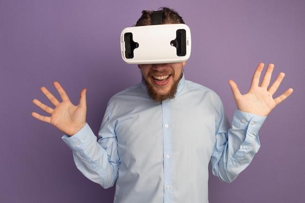 Freudiger hübscher blonder mann mit vr headset steht mit erhobenen händen lokalisiert auf lila wand