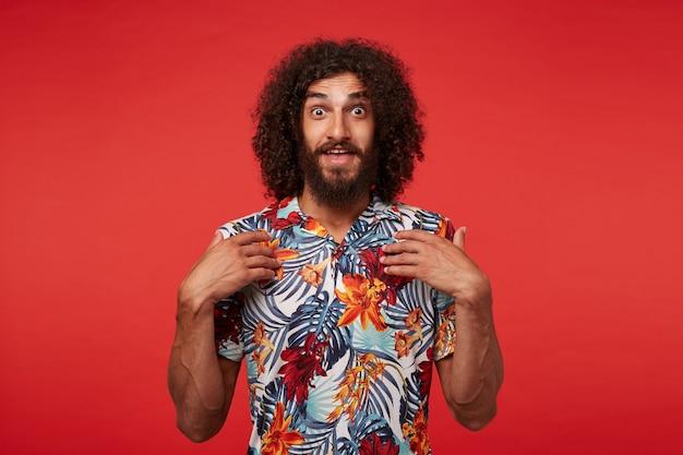 Freudiger hübscher braunäugiger brünetter kerl mit langen lockigen haaren, die überraschend zur kamera schauen und handflächen auf seiner brust halten, gegen roten hintergrund im hemd mit blumendruck posierend