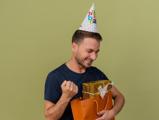 Freudiger hübscher kaukasischer mann, der geburtstagskappe trägt, hält faust und hält geschenkbox in papiereinkaufstasche lokalisiert auf olivgrünem hintergrund mit kopienraum