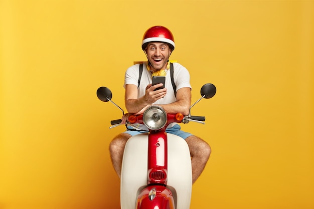 Freudiger hübscher männlicher fahrer auf roller mit rotem helm