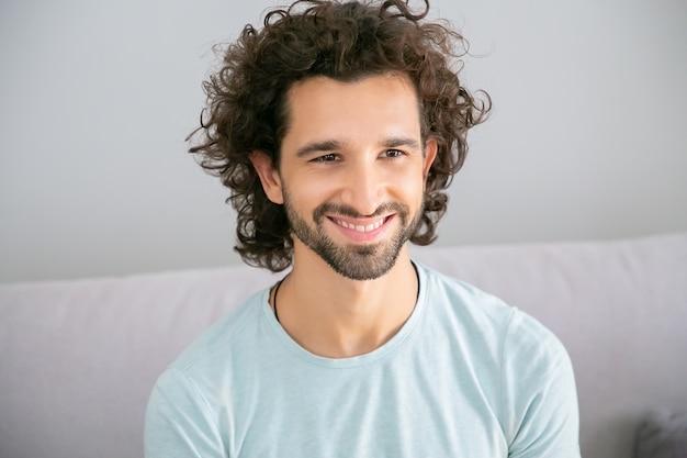 Freudiger hübscher mann mit lockigen haaren, der ein lässiges t-shirt trägt, zu hause auf der couch sitzt, wegschaut, lächelt und lacht. männliches porträtkonzept