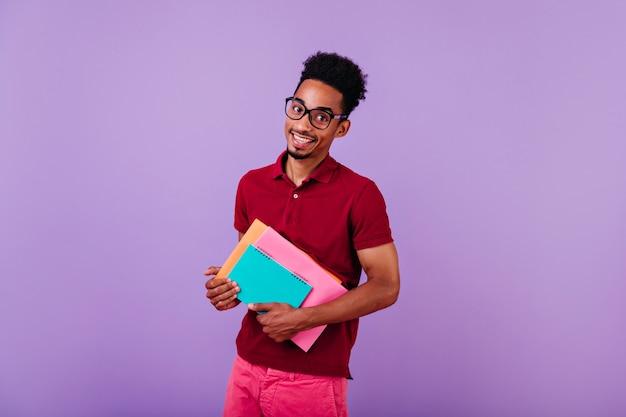Freudiger internationaler student in großen gläsern suchen. innenporträt des intelligenten afrikanischen kerls trägt rotes t-shirt, das mit lehrbüchern aufwirft.