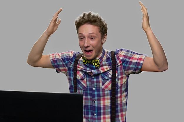 Freudiger jugendlich junge, der laptop betrachtet und erfolg feiert. erfolgreicher junge mit laptop auf grauem hintergrund. siegeskonzept.