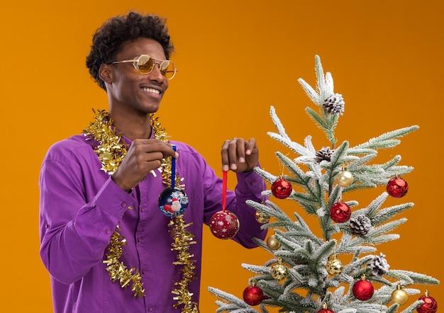 Freudiger junger afroamerikanischer mann, der brille mit lametta-girlande um den hals trägt, der nahe verziertem weihnachtsbaum auf orange hintergrund steht