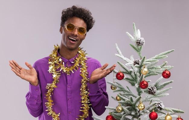 Freudiger junger afroamerikanischer mann, der eine brille mit lametta-girlande um den hals trägt, der nahe verziertem weihnachtsbaum steht, der leere hände lokalisiert auf weißer wand zeigt
