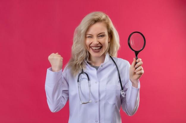 Freudiger junger arzt, der stethoskop im medizinischen kleid trägt, das lupe auf rotem hintergrund hält