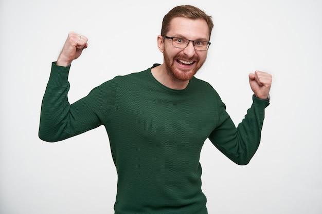 Freudiger junger attraktiver brünetter bärtiger mann mit kurzem haarschnitt, der glücklich mit breitem lächeln und in fäusten gefalteten erhobenen händen steht und steht