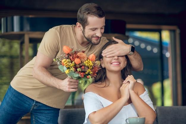 Freudiger junger bärtiger mann mit blumenstrauß, der augen der lächelnden frau bedeckt, die im café sitzt