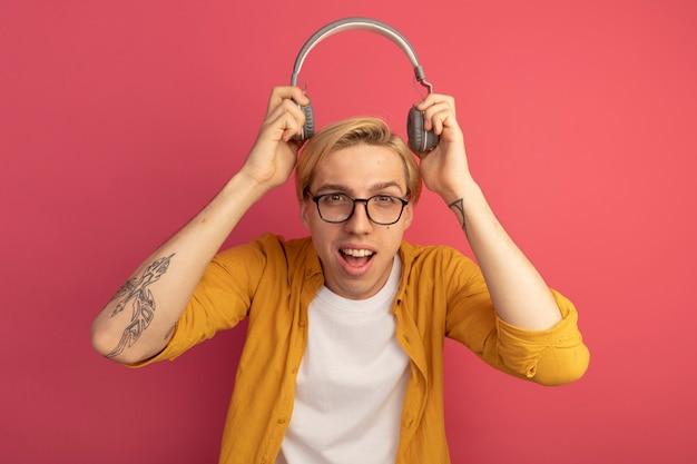 Freudiger junger blonder kerl, der gelbes t-shirt und brille trägt, die kopfhörer auf kopf isoliert auf rosa setzen