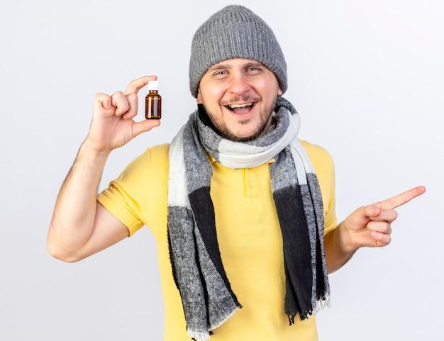 Freudiger junger blonder kranker slawischer mann, der wintermütze und schal trägt, hält medizin in der glasflasche, die zur seite zeigt, die auf weißer wand mit kopienraum lokalisiert wird