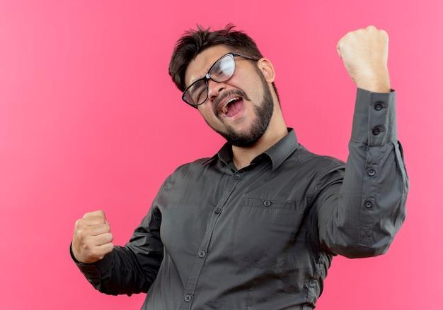 Freudiger junger geschäftsmann, der brillen trägt, die starke geste tun, die auf rosa wand lokalisiert wird
