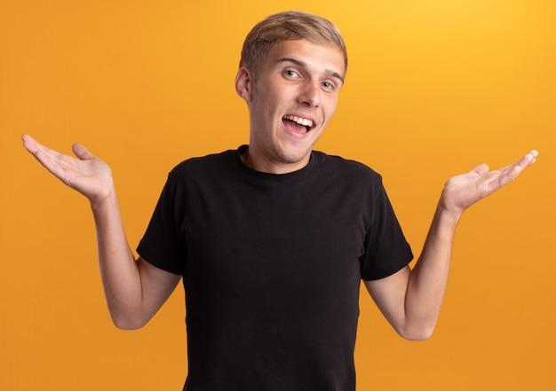 Freudiger junger gutaussehender kerl, der schwarzes hemd trägt, das die hände lokalisiert auf gelber wand spreizt