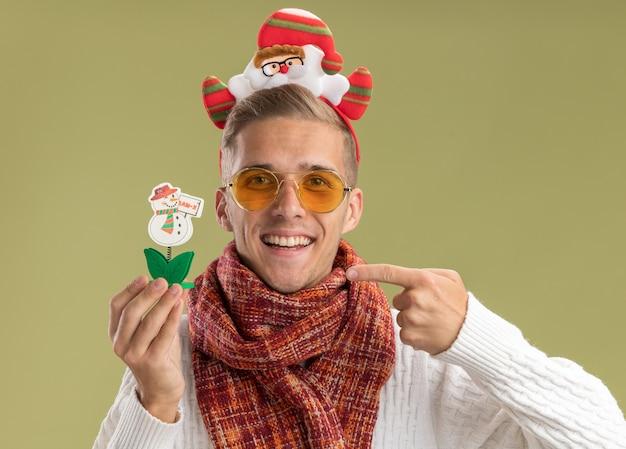 Freudiger junger gutaussehender kerl, der weihnachtsmann-stirnband und schal trägt, die kamera hält und auf schneemannspielzeug zeigt, das auf olivgrünem hintergrund lokalisiert wird