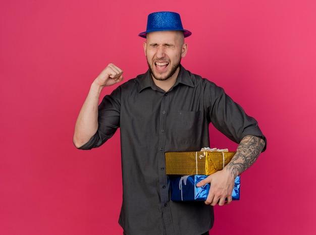 Freudiger junger gutaussehender slawischer party-typ, der partyhut hält, der geschenkverpackungen hält, die ja geste lokalisiert auf purpurrotem hintergrund mit kopienraum tun