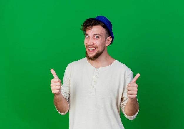 Freudiger junger gutaussehender slawischer party-typ, der partyhut trägt, der front zeigt, zeigt daumen hoch lokalisiert auf grüner wand mit kopienraum